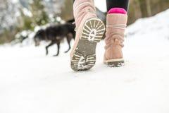 Chaussures d'hiver d'une femme marchant sur la neige Image stock