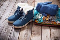 Chaussures d'hiver, gants, écharpes sur le vieux fond en bois photo libre de droits