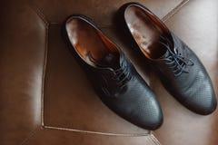 Chaussures d'homme sur une chaise en cuir photos libres de droits