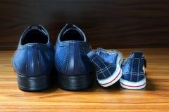 Chaussures d'hommes et espadrilles d'enfants côte à côte sur le plancher en bois Photographie stock libre de droits
