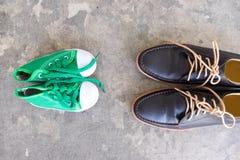 Chaussures d'hommes et espadrilles d'enfants se tenant faisantes face à chacun Images libres de droits