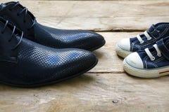 Chaussures d'hommes et espadrilles d'enfants se tenant se faisantes face sur un bois Photo stock