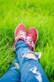 Chaussures d'une femme d'adolescent sur le champ d'herbe Photo stock