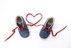 Chaussures de bébé avec des dentelles formant le coeur sur le fond blanc Image stock