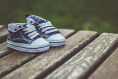 Chaussures de bébé garçon sur un banc Images stock