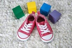 Chaussures de bébé mignonnes et cubes colorés avec l'endroit images libres de droits
