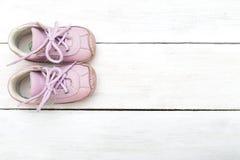 Chaussures de bébé roses pour des filles sur un fond en bois blanc Photo libre de droits