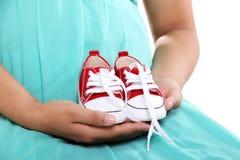 Chaussures de bébé sur le mother& enceinte x27 ; mains de s Images libres de droits