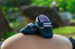 Chaussures de bébé sur le ventre de la femme enceinte photographie stock libre de droits