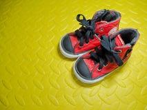 Chaussures de bébé sur les protections en caoutchouc de feuille en caoutchouc photographie stock libre de droits