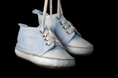 Chaussures de bébé sur un fond noir Images libres de droits