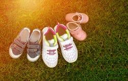 Chaussures de bébé trois paires dans l'herbe - un symbole des enfants dans la famille Photographie stock
