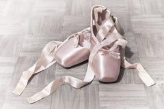 Chaussures de ballet roses sur le plancher de parquet photos stock