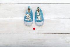 Chaussures de bleus layette sur le fond en bois Configuration plate Photo stock