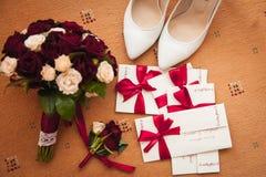 Chaussures de bouquet et de demoiselle d'honneur de mariage, boutonniere sur un tapis brun Images libres de droits