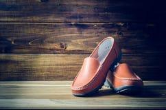 Chaussures de Brown sur le plancher en bois Photographie stock libre de droits