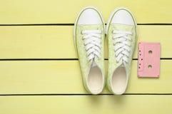 Chaussures de cassette sonore et d'espadrilles sur un fond en pastel jaune Technologies démodées Vue supérieure Configuration pla image libre de droits