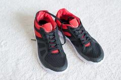 Chaussures de course avec l'équilibre rouge plat sur le plancher Photos libres de droits