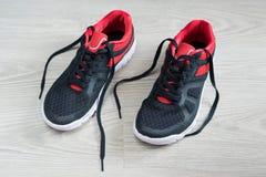 Chaussures de course avec l'équilibre rouge plat sur le plancher Images libres de droits