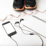 Chaussures de course, bande de mesure, carnet et téléphone Photo libre de droits