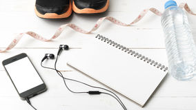 Chaussures de course, bande de mesure, eau potable, carnet et téléphone Photographie stock