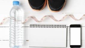 Chaussures de course, bande de mesure, eau potable, carnet et téléphone Photo libre de droits