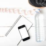 Chaussures de course, bande de mesure, eau potable, carnet et téléphone Photo stock