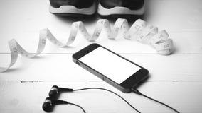 Chaussures de course, bande de mesure et colo noir et blanc de ton de téléphone Image libre de droits