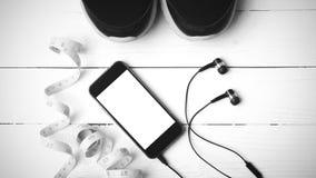 Chaussures de course, bande de mesure et colo noir et blanc de ton de téléphone Photo libre de droits
