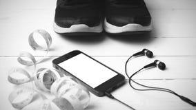 Chaussures de course, bande de mesure et colo noir et blanc de ton de téléphone Image stock