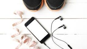 Chaussures de course, bande de mesure et téléphone Image stock
