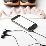Chaussures de course, bande de mesure et téléphone Photographie stock libre de droits