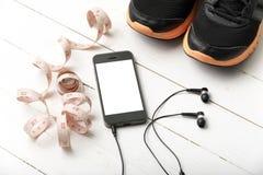 Chaussures de course, bande de mesure et téléphone Images stock
