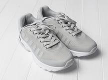 Chaussures de course confortables grises se reposant sur le bois Images stock