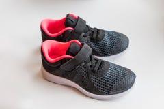 Chaussures de course du ` s d'enfants Nouvelles chaussures roses noires de sport sur le fond blanc chaussures d'enfants d'isoleme Images libres de droits