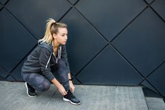 Chaussures de course de essai de femme d'athlète étant prêtes pour pulser dehors dans la ville photos libres de droits