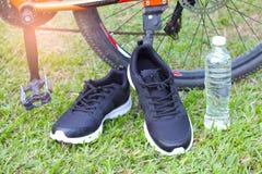Chaussures de course et bouteille noires de l'eau devant la roue de bicyclette sur l'herbe verte Photographie stock