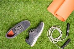 Chaussures de course et corde à sauter pour former, sur un fond d'herbe images stock