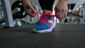 Chaussures de course - femme attachant des dentelles de chaussure dans le gymnase banque de vidéos