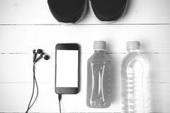 Chaussures de course, jus d'orange, eau potable et noir et wh de téléphone Photographie stock libre de droits