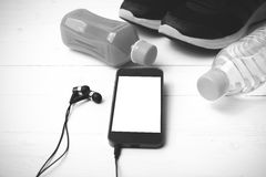 Chaussures de course, jus d'orange, eau potable et noir et wh de téléphone Image stock
