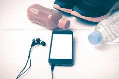 Chaussures de course, jus d'orange, eau potable et ton de vintage de téléphone Image stock