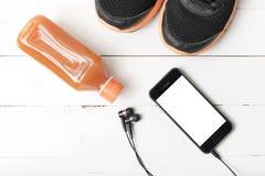 Chaussures de course, jus d'orange et téléphone Images stock