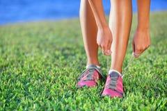 Chaussures de course - plan rapproché de femme attachant des dentelles de chaussure Photographie stock libre de droits