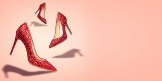 Chaussures de femmes de concept avec l'espace de copie sur le fond rouge Photographie stock libre de droits