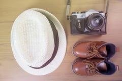 Chaussures de garçon avec l'appareil-photo sur le fond en bois Photos stock