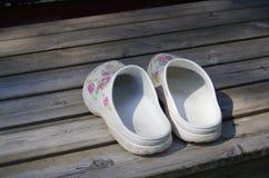 Chaussures de jardin sur une terrasse en bois image stock