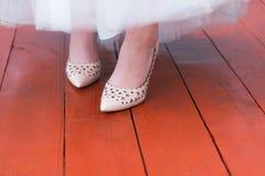 Chaussures de jeune mariée et robe de mariage sur une route en bois rouge photographie stock libre de droits