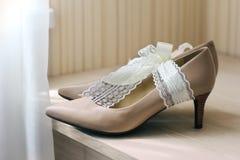 Chaussures de jeune mariée sur la table à côté de la fenêtre image libre de droits
