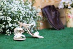 Chaussures de jeunes mariés de mariage avec le fond de décorations Photographie stock libre de droits